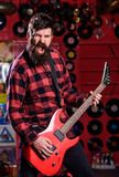 Guitarist on shouting face playing electric guitar on stage. Dark background, night club interior, spotlights royalty free stock photos