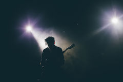 Guitarist silhouette on a stage. In a backlights playing rock music Stock Photos