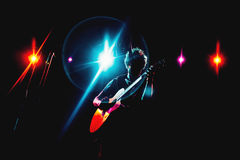 Guitarist silhouette on a stage. In a colorful backlights Stock Image