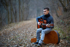 Guitarist singing outdoor in the forest Stock Photo