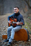 Guitarist singing outdoor in the forest Stock Photos
