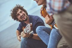 Guitarist singing a song to his friends. Heartwarming melody. Portrait of musician singing a song to his friends while playing the guitar royalty free stock image