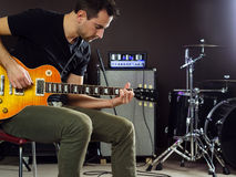 Guitarist sitting and playing on stage Royalty Free Stock Image