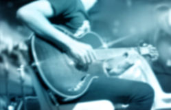 Guitarist on stage, blue tone soft and blur for background Royalty Free Stock Photography