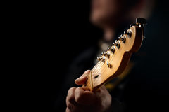 Guitarist on stage. Closeup with selective focus on guitar head Stock Photo