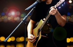 Guitarist on stage performing with acoustic guitar Stock Photo