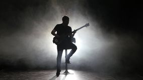 Guitarist strums a leisurely melody sitting on a high chair stock footage