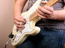 Guitarist in studio. Hand of guitarist playing at white electric guitar Royalty Free Stock Image