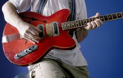 Guitarist in studio. Guitarist with red electric guitar play music in audio studio Stock Photo