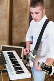 Guitarist  in the studio playing guitar next to the keyboards Stock Photo