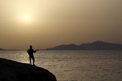 Guitarist at sunrise on the beach Royalty Free Stock Photography