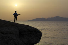 Guitarist at sunrise on the cliff Royalty Free Stock Images