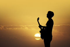Guitarist at sunset Stock Images