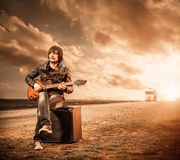 Guitarist at sunset road Stock Photography
