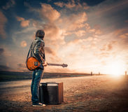 Guitarist at sunset road Royalty Free Stock Images