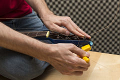 Guitarist using the string winder. Guitarist is using the string winder to tune the guitar faster. (Series with the same model available Stock Photos