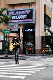 A street guitarist. A guitarist walked across a street in Malioboro area. Malioboro is the most famous shopping destination in Yogyakarta. As one of an economic Stock Photos