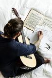 Guitarist writing song in bed Stock Photo