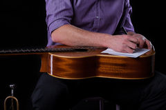 Guitarist writing a song. Close-up of a guitarist writing a song, horizontal Royalty Free Stock Photos