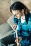 Guitariste beau réfléchi jouant son instrument de musique images stock