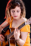 Guitariste féminin avec des dreadlocks jouant la guitare Photographie stock libre de droits