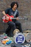 Guitariste jouant dans la ruelle de brique Images stock