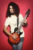 Guitariste passionné jouant avec le beau long jeu de cheveux bouclés Photo libre de droits