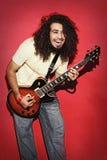 Guitariste passionné riant avec de longs cheveux bouclés de joie jouant g Photo libre de droits