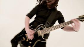 Guitariste solo élégant avec des tresses rastas sur la tête et en vêtements noirs sur fond blanc jouant expressivement banque de vidéos