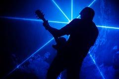 Guitariste sur un fond des lumières Photos stock