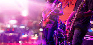 Guitarists and colorful lighting on a stage, soft focus royalty free stock photos