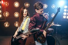 Guitarists plays on electric and bas guitar. Stage with lights on background. Rock band concert Royalty Free Stock Photos