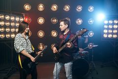 Guitarists plays on electric and bas guitar. Stage with lights on background. Rock band Stock Images