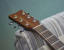 Guitarra acústica clásica del instrumento musical del color claro con las clavijas de acero y las secuencias de plata imagenes de archivo