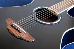 Guitarra acústica com parte superior preta com os seis close up das cordas Fotografia de Stock