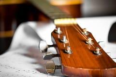 Guitarra acústica con la nota de la canción Fotos de archivo