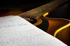 Guitarra acústica con la nota de la canción Imagenes de archivo