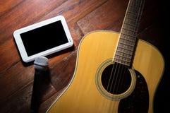 Guitarra acústica con la tableta del micrófono y del ordenador Foto de archivo