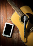 Guitarra acústica con la tableta del micrófono y del ordenador Fotos de archivo