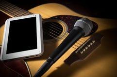 Guitarra acústica con la tableta del micrófono y del ordenador Fotografía de archivo libre de regalías
