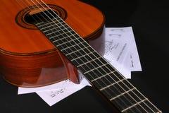 Guitarra acústica con las hojas de música Imagenes de archivo