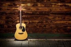 Guitarra acústica de encontro às portas oxidadas foto de stock