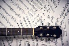 Guitarra acústica do Fingerboard em notas de uma folha do fundo fotos de stock