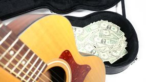 Guitarra acústica dobrada fora de foco, caso com dinheiro no foco, profundidade de campo forte imagem de stock