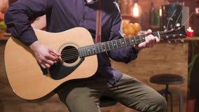 Guitarra acústica e mãos masculinas que jogam nela