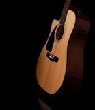 Guitarra acústica em um fundo preto Fotos de Stock