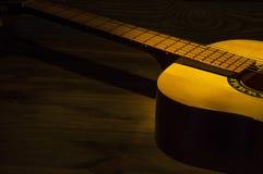 Guitarra acústica em uma tabela de madeira iluminada por um raio de luz foto de stock