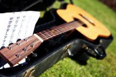 Guitarra acústica en caso de que con música Foto de archivo