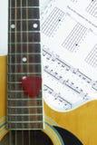 Guitarra acústica en la hoja de la nota de la música Imágenes de archivo libres de regalías