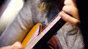 Guitarra acústica hermosa del primer que es jugada por la mujer que se sienta, concepto del músico Mujer que juega el primer de l almacen de metraje de vídeo